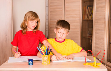 Sister helping her brother with home assignment. children doing homework.