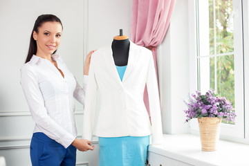 Cheerful young modern tailor is creating new costume