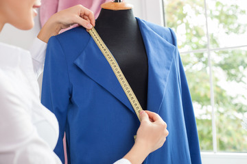 Attractive young modern tailor is creating new clothing