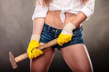 Closeup of sexy woman holding hammer. Feminism.