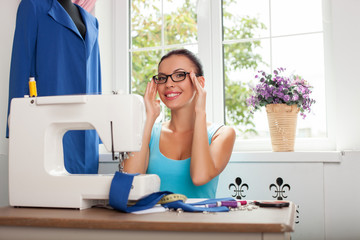 Beautiful young fashion designer is creating new clothing