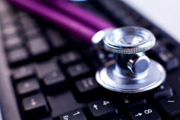 Medical stethoscope lying on a computer keyboard, a cup of