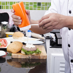 Chef putting mayonnaise on the Hamburger bun
