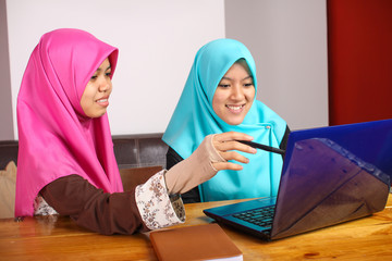 two young muslim women with laptop