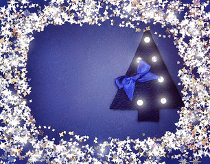 Christmas tree in a frame of sequins on a blue background.