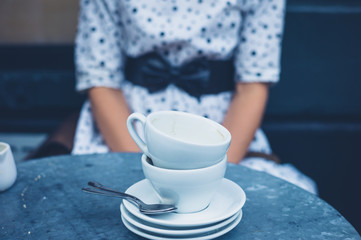 Woman at table with empty coffee cups