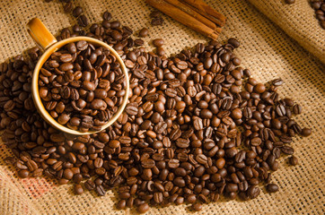 Roasted coffee beans and a cup and around