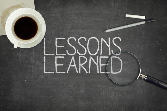 Lessons learned concept on black blackboard