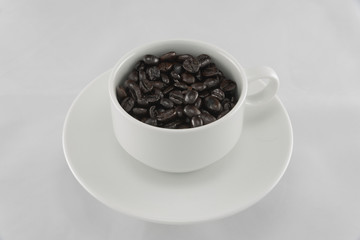 coffee beans in the cup on white background.