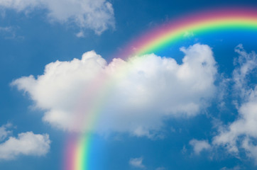 Rainbow and White clouds in blue sky background
