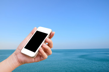 woman hand holding the phone tablet on wide angle view of seasca