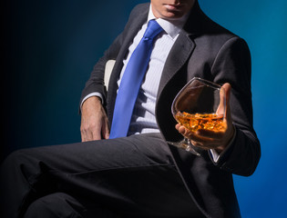 A man sits on a chair with a glass of cognac
