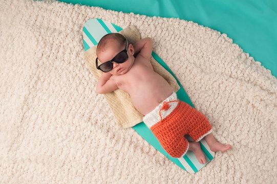 Newborn Baby Boy Sleeping on a Surfboard