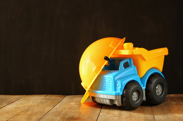 Dump truck toy and safety hat over wooden textured background