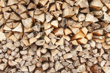 Ready firewood. Various kinds of wooden logs stacked on top of each other. Stack of wood, firewood, background. Dry chopped firewood logs ready for winter.