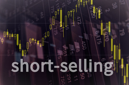 """Downtrend stock chart on PC screen and inscription """"Short-selling""""."""