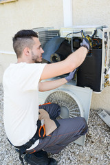 handsome young man electrician installing air conditioning in a client house
