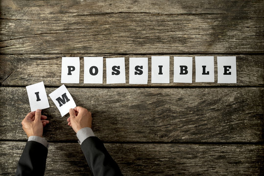 Businessman taking away letters IM from the word impossible changing it into possible spelled on individual white cards lying on cracked old wooden desk. Conceptual of positive attitude.