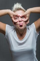 Beautiful young woman making a funny face. Studio shot.