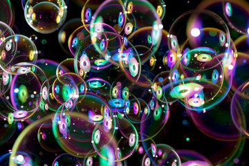 colorful soap bubbles flying around on black background