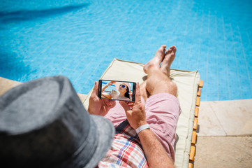 man in a hat lying on a lounger with a smartphone