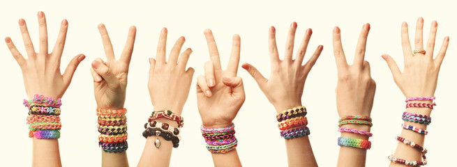 People's hands with braceles on light background