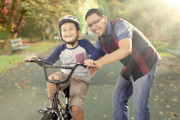 Boy exercises to ride a bike with his dad