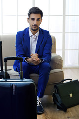 Business man with suitcases sitting on sofa in hall