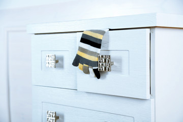 White wooden chest of drawer with sock in opened drawer