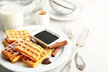 Sweet homemade waffles on plate, on light background