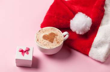 Cup of coffee with heart shape and christmas gift