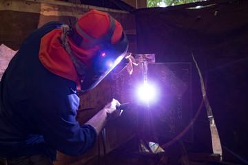 Worker is welding on the steel plate