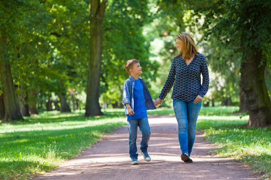 young woman with son walking through avenue
