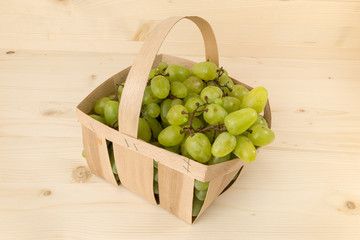 Muskat grapes in a wooden backet on a wooden background