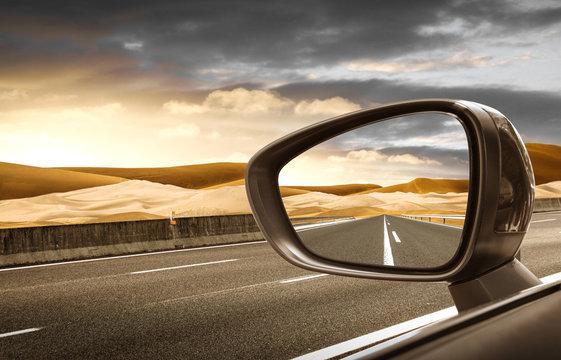 strada nel deserto riflessa nello specchietto retrovisore esterno
