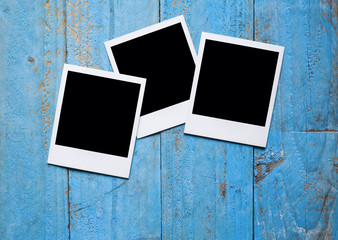 Blank instant photo frames on old blue wooden background