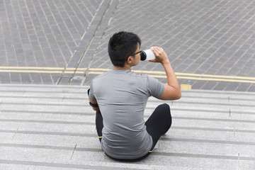 Asian man drinking while exercising outdoors.