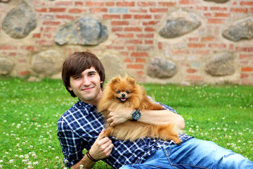 Handsome happy man with cute pomeranian dog lying on the green grass. Man and his lovely dog. Love of animals. Dog man's best friend
