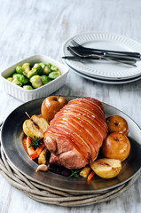 Roasted pork on a bed of vegetables and baked apples