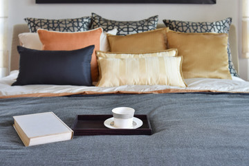 modern bedroom interior with teacup on decorative wooden tray an
