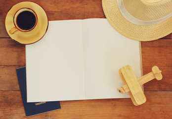 top view image of open notebook with blank pages, cup of coffee wicker hat