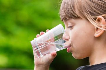Child drinking glass of fresh water