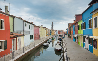 Burano island in Venice with colorful houses and boats, Italy