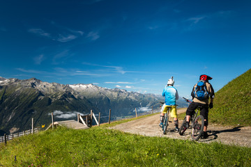 enduro bikers starting trail riding in austrian alps with mountain view on wildkogel