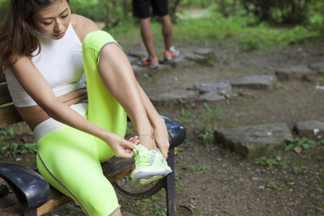 Women are wearing sports shoes on a bench in the park