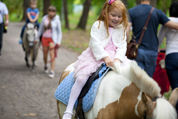 Little girl riding on a pony in a city park