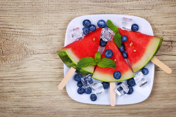 Watermelon popsicle and blueberries on old wooden background