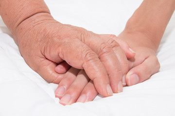 Elderly woman holding a young hand