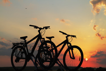 Bikes on top of a car against sunset.