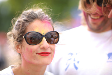 Attractive woman in sunglesses with painted face, celebration of holi festival